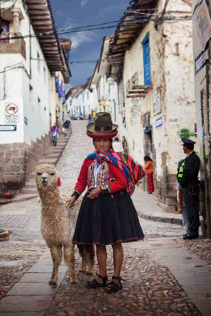 A woman wear traditional clothing in Cusco poses with her llama, Peru
